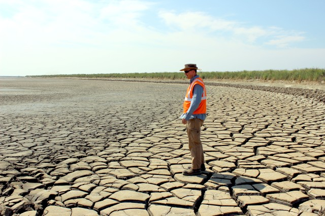 Seth Keller, biologist for the Army Corps of Engineers, stands on the crust of a drying upland cell on Poplar Island. The eroding Chesapeake Bay island has been restored from 4 to more than 1,000 acres using dredged materials. Here the silt dries in the sun before grading and planting -- a process that takes years.