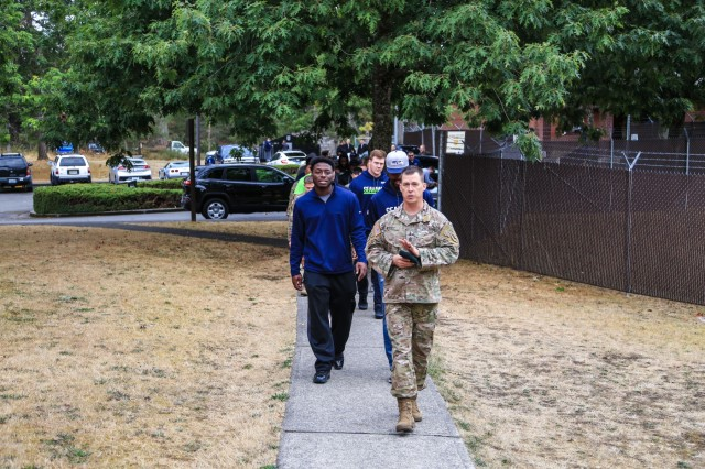 Command Sgt. Maj. Tony Labrec, the senior enlisted leader of the 1st Special Forces Group (Airborne,) guides members of the Seattle Seahawks on a tour at Joint Base Lewis-McChord, WA., September 19, 2017. CSM Labrec took the Seahawks from the 1st Special Forces Memorial Wall to the Regimental Mess Facility as part of their visit to the group compound. (U.S. Army photo by Sgt. Wes Conroy/Released).
