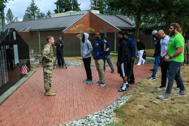 Col. Guillaume Beaurpere, Commander of the 1st Special Forces Group (Airborne,) greets members of the Seattle Seahawks as they arrive to Joint Base Lewis-McChord, WA., September 19, 2017. Col. Beaurpere began the Seahawks tour of the group compound with a visit to the 1st Special Forces Memorial Wall, which is dedicated in honor of the Soldiers who have sacrificed their lives while assigned to 1st SFG (A).  (U.S. Army photo by Sgt. Wes Conroy/Released).
