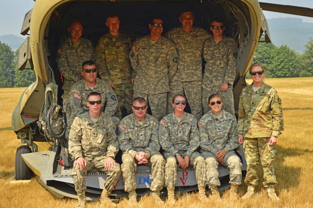 Members of Bravo Company, 1st Battalion, 168th Aviation Regiment, gather together on the ramp of one of their CH-47 Chinook helicopters at Davis helibase near Gates, Oregon, on August 9, 2017. More than 20 personnel, including pilots, flight crew, fuelers and maintainers were called upon to support state and federal agencies at the Whitewater Fire burning in the Mount Jefferson Wilderness Area.