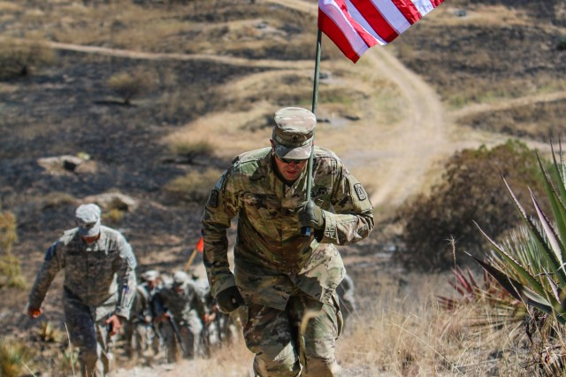 Master Sgt. James Goss, Alpha Company, 40th Expeditionary Signal Battalion, carries the colors and leads the charge to take the hill on Range 1B upon the conclusion of daytime operations for their field training exercise Sept. 20, 2017.