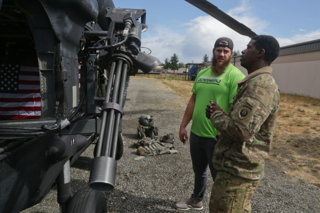 Seattle Seahawks offensive lineman Jordan Roos talks with a member of the 160th Special Operations Aviation Regiment (Airborne) at Joint Base Lewis-McChord, Wash., Sept. 19, 2017. The UH-60 Blackhawk helicopter was one of two aircrafts on display for the Seattle Seahawks members to see. (U.S. Army photo by Sgt. Codie Mendenhall/Released)