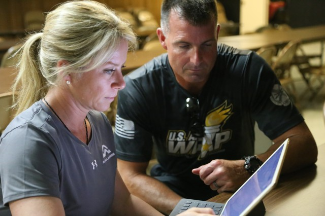 "Coach Brandi Binkley, with co-coach Capt. Mike Kohn of the U.S. Army World Class Athlete Program, strategize during a community service event with Team ""Able"" as they prepare for the BOSS Strong Championship finale in San Antonio, Texas. The Army invited coaches from industry to assist in their program toward Soldier functional fitness. Photo by Robert Dozier, IMCOM Public Affairs"