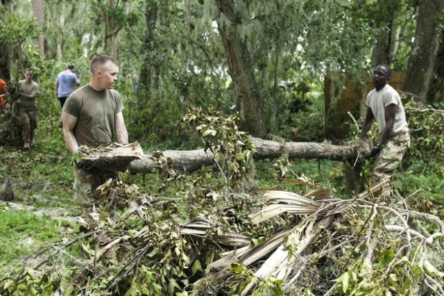 Army Sgt. Kenneth Douglas, right, and Spc. Zephaniah Koech carry a downed tree branch clearing debris in Lakeland, Fla., Sept. 15, 2017, during cleanup efforts in Hurricane Irma's aftermath. Douglas is assigned to the 82nd Airborne Division. Koech is assigned to the 3rd Expeditionary Sustainment Command.