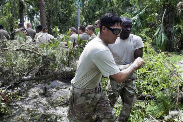 Army Spcs. Travis Rahmin, left, and Zephaniah Koech drag a downed tree branch clearing debris in Lakeland, Fla., Sept. 15, 2017, during cleanup efforts in Hurricane Irma's aftermath. Rahmin is assigned to the 82nd Airborne Division. Koech is assigned to the 3rd Expeditionary Sustainment Command.