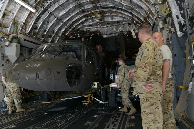 Members of the Missouri Army National Guard watch a UH-60 Black Hawk helicopter get loaded onto a C-17 Globemaster III prior to being transported from Whiteman Air Force Base, Mo., to the Virgin Islands, Sept. 24, 2017. Elements of the Missouri National Guard have been activated to support hurricane relief efforts.