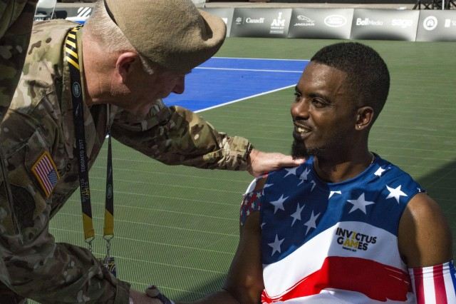 Army Gen. Raymond A. Thomas III, commander of U.S. Special Operations Command, shakes hands with Roosevelt Anderson, a medically retired Army Special Forces sergeant, after a tennis match at the Invictus Games in Toronto, Sept. 23, 2017.