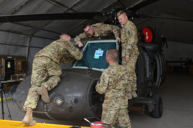 Soldiers of Company B, 2nd Battalion, 10th Combat Aviation Brigade, operating out of Camp Mihail Kogalniceanu, Romania, replace a windshield on a Black Hawk helicopter, Sept. 18, 2017.