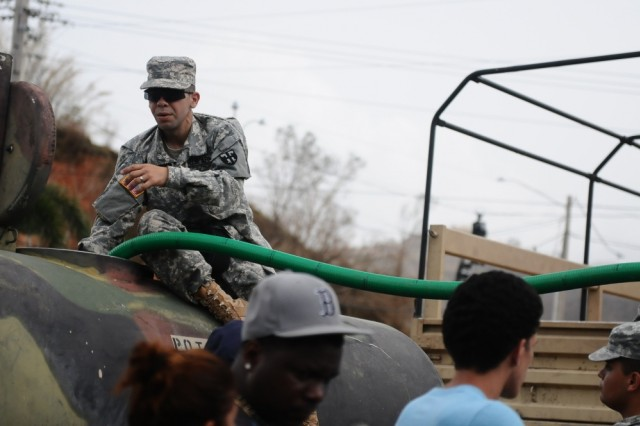 Guardsmen from the Puerto Rico National Guard, along with employees from the Aqueducts and Sewers Authority of Puerto Rico, distribute water for the communities of Utuado, Puerto Rico, Sept. 26. After the impact of Hurricane Maria, 2,175 service members, including the PRNG, had been mobilized in the territory to support the efforts of the government in the reconstruction of the island.
