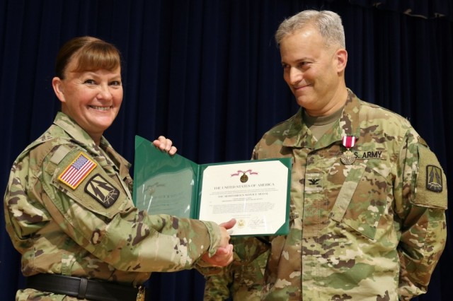 U.S. Army Col. Michael D. Smith, former commander of the new Army Reserve Cyber Operations Group, 335th Signal Command (Theater), receives the Army Meritorious Service Medal, from Brig. Gen. Nikki L. Griffin Olive, deputy commanding general, sustainment command 335th SC (T), during a change of command ceremony September 24 at the Army Research Laboratory, in Adelphi, Maryland. Smith, relinquished command to Col. Robert S. Powell, Jr., who has followed a similar career path as Smith, and will continue working to advance the ARCOG for readiness in cyber capabilities.