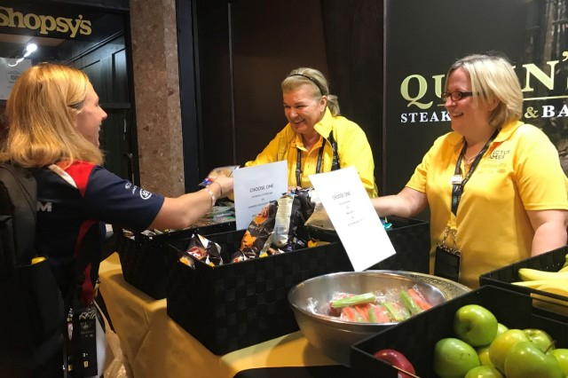 (L-R) Invictus hospitality volunteers Teresa Chorneawski and Lucy Occleshaw help an Invictus attendee at the Sheraton Hotel in downtown Toronto.