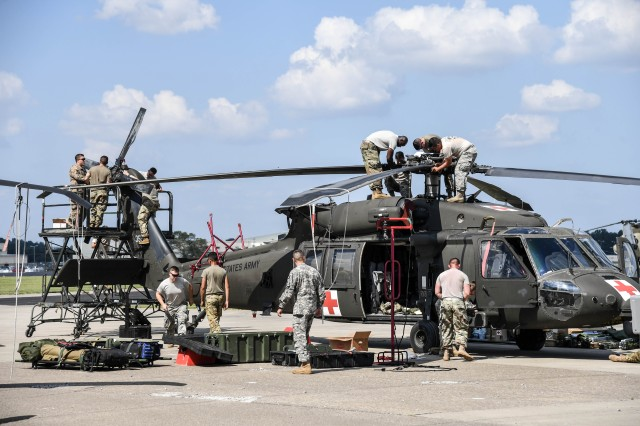 U.S. Army Soldiers assigned to Company C, 6th Battalion, 101st General Support Aviation Battalion, prepare an HH-60 medevac Blackhawk helicopter for transport to Puerto Rico.