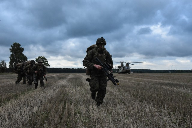 """U.S. Marines from Special Purpose Marine Air-Ground Task Force SPMAGTF Black Sea Rotational Force 17-2 load CH-47's from 1st Bn., 214th Avn. Regt., """"Big Windy,"""" 12th Combat Aviation Brigade during exercise Aurora 17 Sept. 21, 2017 on the island of Gotland, Sweden.  Exercise Aurora 17 is an exercise designed to improve, test and show the capabilities of the Swedish Armed Forces."""