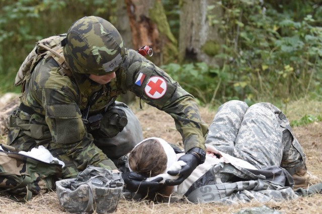 GRAFENWOEHR, Germany- Master Sgt.  Radek Kristof, Czech Army, evaluates a casualty and dress a head wound during the 2017 USAREUR Expert Field Medical Badge testing phase Sept. 26 at Grafenwoehr Training Area. Kristof was one of several international candidates hoping to earn their badge. (U.S. Army photo by Capt. Jerome Ferrin, 30th Medical Brigade Public Affairs)