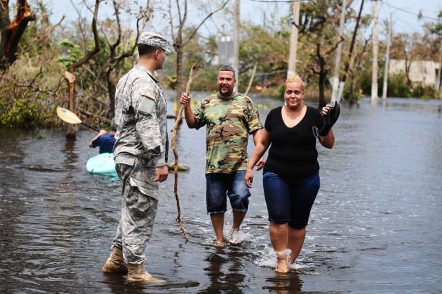 A Soldier helps a man and woman leave a flooded area in Condado, San Juan, Puerto Rico, Sept. 22, 2017, after Hurricane Maria hit the island.
