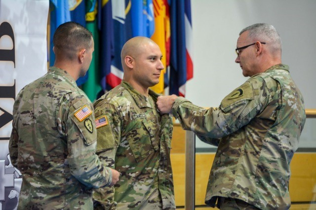 Brig. Gen. Dennis P. LeMaster, Regional Health Command Europe commander, pins Sgt. Ed Cancecorenner, 3rd Squadron, 2d Cavalry Regiment, with the Expert Field Medical Badge at a graduation ceremony hosted at the Grafenwoehr Physical Fitness Center at Tower Barracks, Germany, Sept. 28, 2017.