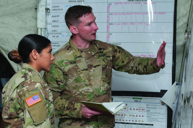 Maj. Alexander Dean, division JAGIC chief, and Capt. Victoria Strait, division current operations battle captain, work inside the tactical command post to open lines of communication with all of the units participating in the war-fighter exercise.