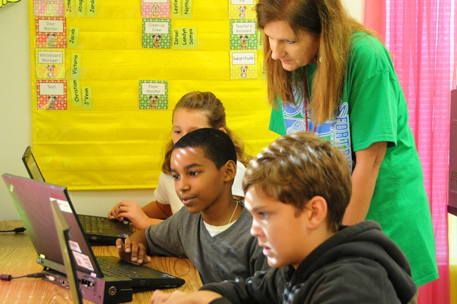 Dr. Vicki Gilmer, principal of Fort Rucker Schools, checks in on students as they work on their assignments in class Friday.