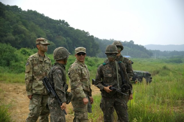 2nd Lt. David Lara stands in the middle of a group of ROK army soldiers and a Korean augmentee to the United States Army to discuss their plan during the first combined short range air defense training exercise between ROK and U.S. air defense artillery units Sept. 7 at the Darrakae training area, Pocheon, South Korea.