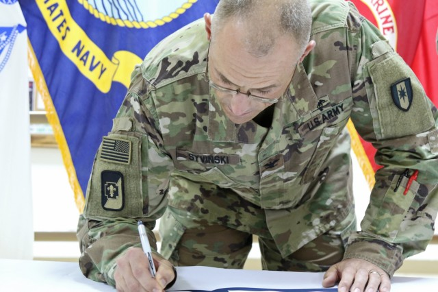 U.S. Army Col. Bruce Syvinski, commander, 86th Combat Support Hospital, sign the memorandum of agreement allowing Red Cross volunteers to work in the combat support hospital, Aug. 31, at Camp Arifjan, Kuwait. Volunteerism is one of the oldest social practices in America which strengthen communities by increasing one's social and relationship building skills.