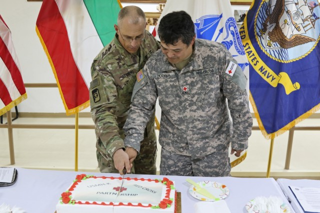 U.S. Army Col. Bruce Syvinski (left), commander, 86th Combat Support Hospital and Mark Hooper (right), regional director at Camp Arifjan American Red Cross, cut the cake marking the start of their partnership program, Aug. 31. Volunteers, working through the Red Cross, can now gain valuable experience and insight into multiple medical fields at this military treatment facility.