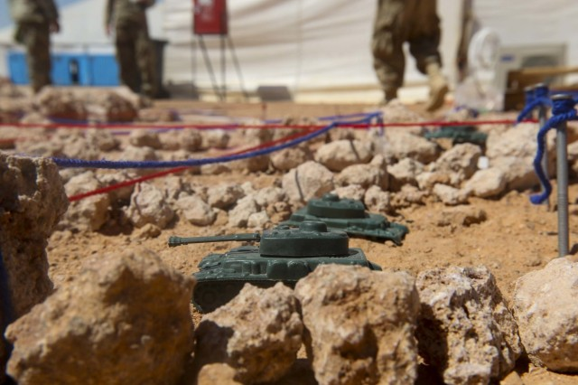 Toy tanks depicting the friendly and enemy elements on the battlefield are placed into strategic positions on a terrain model at the field training site at the Mohamed Naguib Military Base, Egypt, Sept. 9. The terrain model allows the unit to rehearse its actions and movements on a replica of the battlespace to ensure they are prepared for any eventuality. (U.S. Army photo by Staff Sgt. Leah R. Kilpatrick)