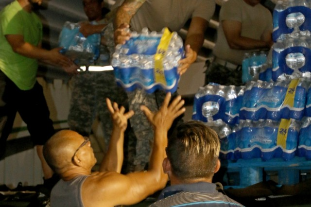 Soldiers assigned to 1st Mission Support Command, in Ceiba, Puerto Rico, distribute bottles of water to local volunteers in Florida, Puerto Rico, Sept. 30, 2017. The Department of Defense and is supporting the Federal Emergency Management Agency in helping those affected by Hurricane Maria to minimize suffering as part of the overall whole-of-government response efforts.