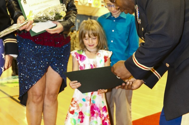 "Col. Frank David II, commander of 71st Ordnance Group (Explosive Ordnance Disposal), gives the daughter of Col. Michael Mahoney, commander of the U.S. Army Dental Activity on post, a certificate for supporting her father's career during a post retirement ceremony Sept. 27, 2017, inside the William ""Bill"" Reed special events center at Fort Carson, Colo. The Mahoney family was one of eight families honored at the ceremony. The ceremony is held each month to show appreciation for Soldiers exiting the military and allows friends, family members and coworkers an opportunity to celebrate in the Soldiers' decades-long achievements. (U.S. Army photo by Staff Sgt. Lance Pounds, 71st Ordnance Group (EOD), Public Affairs)"