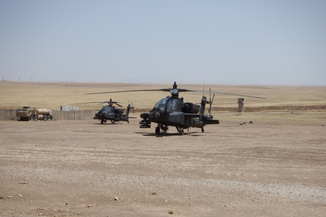 Two AH-64E Apache helicopters sit parked at a forward arming and refueling point (FARP) in Southwest Asia on July 28, 2017. FARPs operated by the 449th Aviation Support Battalion expand the reach and capabilities of aviation assets conducting missions in support of Combined Joint Task Force Operation Inherent Resolve. CJTF-OIR is the global coalition to defeat ISIS in Iraq and Syria.