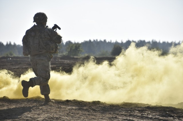 A U.S. Soldier assigned to Battle Group Poland and 2d Squadron, 2d Cavalry Regiment runs after conducting a breach of a mined wire obstacle during a Combined Arms Live Fire Exercise, in Bemowo Piskie Training Area, Poland, Oct. 1-3, 2017. The Soldiers from the Engineer Squadron, 2CR built the 900 meter long trench for the CALFEX in order to create a realistic training environment for a Troop size element. This range will continue to be used by Polish and U.S. Army forces.