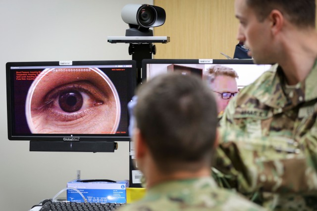 In a demonstration of the Telehealth process at Fort Campbell's Blanchfield Army Community Hospital, clinical staff nurse Lt. Maxx P. Mamula examines patient Master Sgt. Jason H. Alexander using a digital external ocular camera. The image is immediately available to Lt. Col. Kevin A. Horde, a provider at Fort Gordon's Eisenhower Medical Center, offering remote consultation.