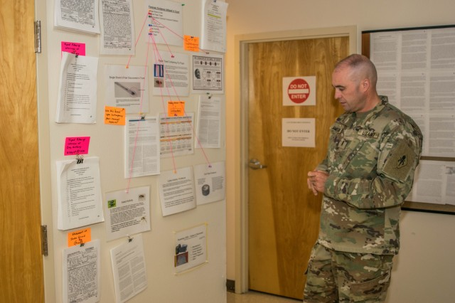 Chief Warrant Officer 3 Kelly Jameson looks at a board he keeps filled with high-profile national cold cases.