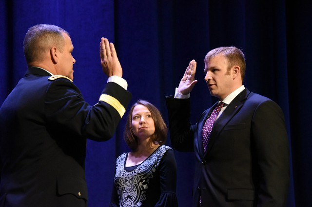 Lt. Gen. James Dickinson, commanding general, U.S. Army Space and Missile Defense Command/Army Forces Strategic Command, administers the oath to Dr. Craig Robin, senior research scientist for directed energy applications, SMDC's Technical Center, during Robin's appointment ceremony at the Von Braun III auditorium Oct. 4 while Robin's wife, Jennifer Hejtmanek, looks on. The Department of the Army created this position within SMDC to focus on directed energy. Robin is one of only 36 senior scientific professionals in the Army.