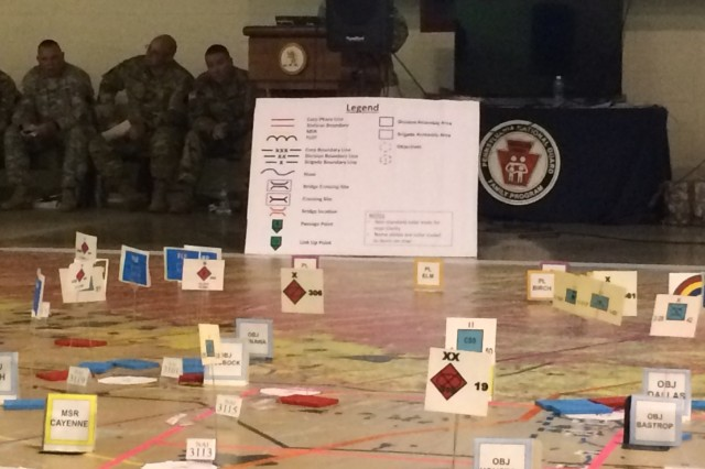 Cardboard markets indicate enemy units and objectives on a giant map at Fort Indiantown Gap, Pennsylvania on Oct. 4, 2017, as leaders of the New York Army National Guard's 42nd Infantry Division conduct a Rehearsal of Concept exercise during their Warfighter exercise. Leaders move markers representing their units and discuss their actions at that phase of the battle to ensure that all leaders and staff understand the plan.