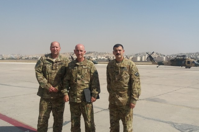 Maj. Robert Bugner (left), Chief Warrant Officer 4 John Silva (center) and Chief Warrant Officer 2 Melvin Marrero-Acevedo (right), pose for a photo in front of a Royal Jordanian Air Force Squadron 8 UH-60 Black Hawk helicopters at Amman, Jordan, Sept. 12. Soldiers from the 29th Combat Aviation Brigade participated in a power management and hoist maintenance expert exchange designed to increase the interoperability of both U.S. and Jordanian forces.