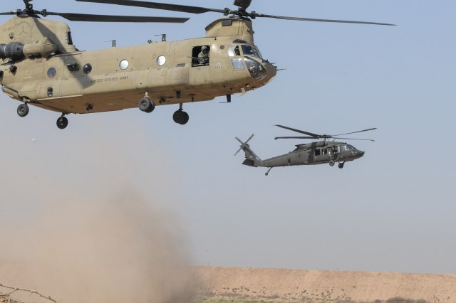 A UH-60M Black Hawk helicopter (right) and a CH-47 Chinook helicopter from 2-149th General Support Aviation Battalion, Task Force Rough Riders, lands prior to inserting Paratroopers from Task Force Red Falcon's Company C,1st Battalion, 325th Airborne Infantry Regiment, 2nd Brigade Combat Team, 82nd Airborne Division, during the aerial response force exercise at Camp Taji Military Complex, Iraq, August 13, 2017.
