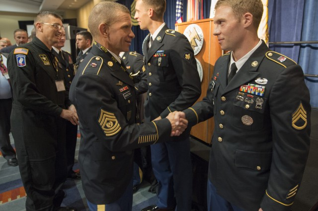 Staff Sgt. Ryan McCarthy, right, and Spc. Hazen Ham, second from right, shake hands with attendees at an award ceremony for Soldier and NCO of the Year at the Association of the U.S. Army's annual meeting and exposition in Washington, D.C., Oct. 9, 2017. Both Soldiers won the Best Warrior Competition, which was held Oct. 1-6 at Fort A.P. Hill, Virginia.
