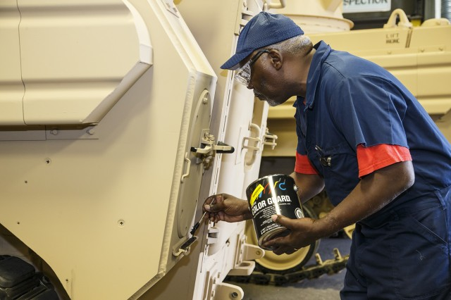 Percy Welch applies color guard to a M113A3/BMP-2 Opposing Forces Surrogate Vehicle in Anniston Army Depot's Upholstery Shop. The depot recently completed overhaul of 14 of these training vehicles.