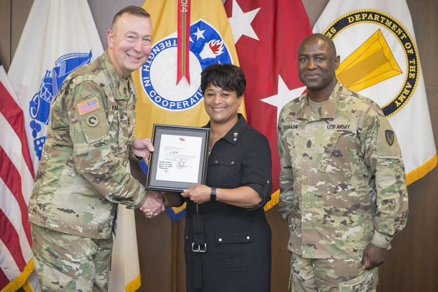 Wanda Chambers accepts a two-star note congratulating her on her USASAC employee of the quarter selection from Maj. Gen. Stephen Farmen, USASAC commander, as Command Sgt. Maj. Gene Canada looks on at a recent town hall meeting. Photo by Michelle Miller
