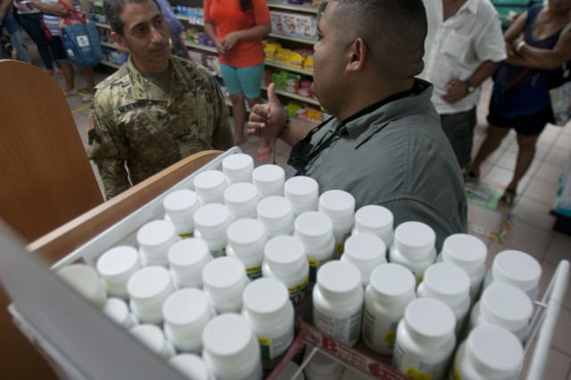 Maj. Manuel Menendez, commander of the 759th Forward Surgical Team, 44th Medical Brigade out of Fort Bragg, North Carolina, currently attached to the 14th Combat Support Hospital, 44th Medical Brigade from Fort Benning, Georgia, talks with Jose Rodriguez, Operations Manager of the Humacao municipality while waiting in line at a pharmacy in Humacao, Puerto Rico Oct. 10, 2017. The Army is supporting FEMA and other federal agencies in life supporting across Puerto Rico in the wake of Hurricane Maria.