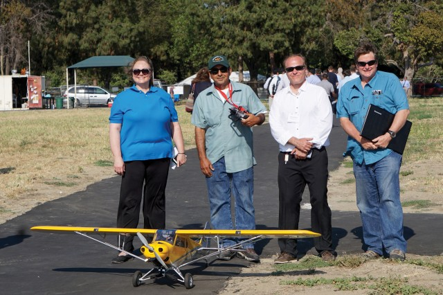 Sara Kambouris, Gilbert Lucero, Jeffrey Wallace and Dean Garvy, of Infinite Dimensions Inc., display a fixed-wing aircraft at Whittier Narrows Airfield in Rosemead, California, that uses the FACE architecture. Infinite Dimensions works on the next generation of systems integration using interoperability, artificial intelligence and virtual reality. (Photo courtesy of the author)