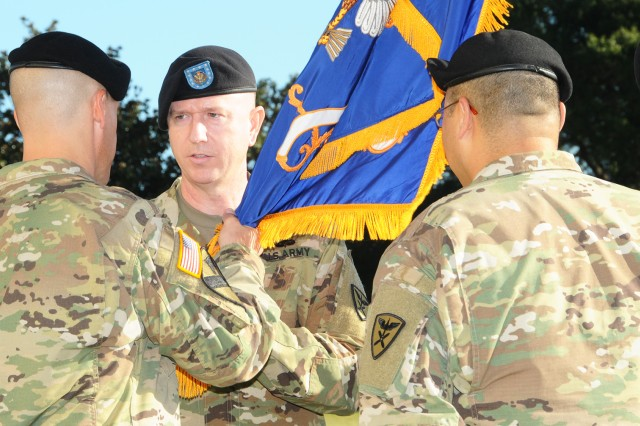 Command Sgt. Maj. James W. Coquat assumes responsibility from Command Sgt. Maj. Michael L. Awai as the unit colors changed hands from Awai to Lt. Col. Cecil C. Nix, 1-212th Avn. Regt. commander, to Coquat, during a change of responsibility ceremony on Howze Field Oct. 6.