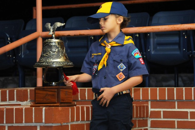 Luca Robishaw, Cub Scout and son of Lt. Col. Chris Robishaw, USAACE Special Operations Element, rings the bell on Howze Field.