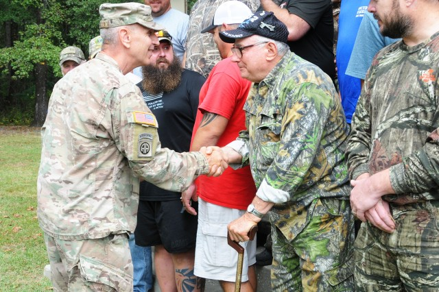 Lt. Col. Scott Wile, Directorate of Public Safety director and provost marshal, presents wounded warriors with a coin during the Wounded Warrior Fall Hunt closing ceremony on West Beach at Lake Tholocco Oct. 7.