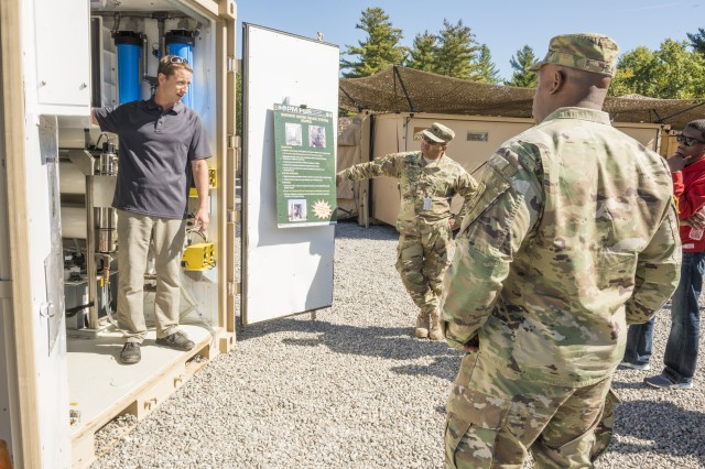 Ryan Eckert, an electrical engineer with Product Manager Force Sustainment Systems, or PM FSS, explains a shower water reuse system Oct. 2 at the Base Camp Integration Laboratory during the 2017 G-4 Professional Development Event hosted by PM FSS.