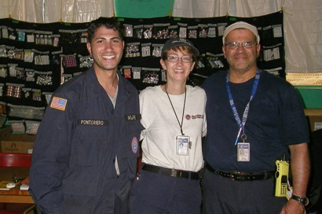 Dr. Shannon Manzi (center) and team members from the Massachusetts -- 1 Disaster Medical Assistance Team, or MA-1 DMAT, out of Boston, deployed to Haiti in support of the international disaster relief efforts to the earthquake in 2010. Dr. Manzi the MREs salt, sugar, and drink flavoring packets to make an emergency oral rehydration solution for dehydrated babies and victims.