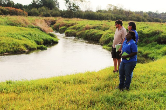 Fisheries Biologist John Noble (center) explains the work that was done on Silver Creek to remove the West Silver Wetland Dam at the site in summer 2017 with U.S. Fish and Wildlife Service personnel, Fisheries Biologist Louise Malden (right) and Project Leader Sam Finney (left). Mauldin and Finney visited Fort McCoy to see progress on stream-habitat and fish-passage improvement projects that have been completed in recent years. (U.S. Army Photo by Scott T. Sturkol, Fort McCoy, Wis.)