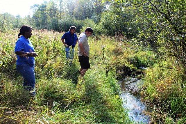 Fort McCoy Fisheries Biologist John Noble (center) explains the work that was done on Stillwell Creek for a stream-restoration project in 2014 with U.S. Fish and Wildlife Service personnel, Fisheries Biologist Louise Malden (left) and Project Leader Sam Finney (right) at Fort McCoy, Wis., on Oct. 3, 2017. Mauldin and Finney visited Fort McCoy to see progress on stream-habitat and fish-passage improvement projects that have been completed in recent years. (U.S. Army Photo by Scott T. Sturkol, Fort McCoy, Wis.)