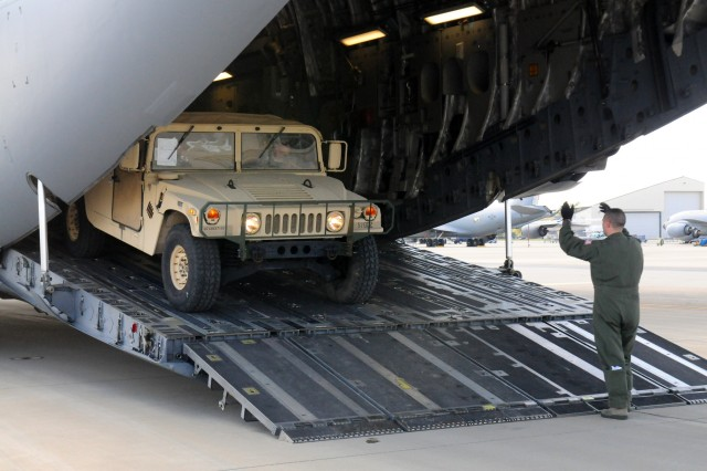 An Airman guides an Ohio Army National Guard Humvee onto a C-17 Globemaster III Oct. 11, 2017, at Rickenbacker Air National Guard Base in Columbus, Ohio. About 40 Soldiers from the 137th Signal Company, based in Newark, Ohio, are deploying to Puerto Rico to provide communications support to hurricane relief efforts.