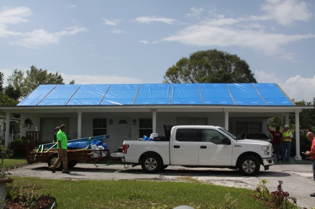 """SEBRING, Fla. -- Contractors pack up materials and gear after installing fiber-reinforced plastic sheeting on a Hurricane Irma-damaged roof in Sebring, Florida Oct. 1, 2017.  The contractors were hired by the U.S. Army Corps of Engineers for Operation Blue Roof. The program sends out licensed contractors to install blue plastic sheeting on eligible roofs until residents can arrange permanent repairs. As of Oct. 2, 2017, the Corps has installed more than 1300 """"blue roofs"""" across 29 counties in Florida. (U.S. Army photo/Kerry Solan)"""